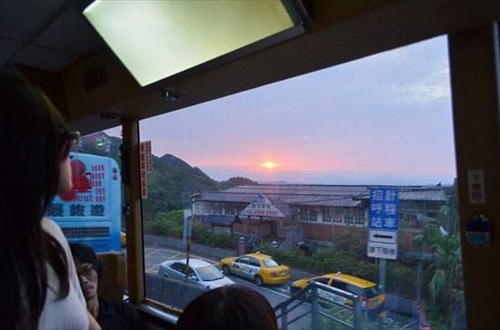 バスの窓から、雲海に沈む夕日を眺める